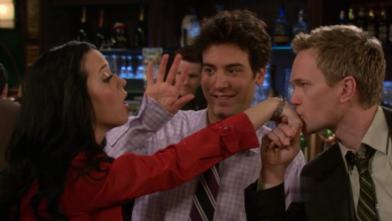 Barney (Neil Patrick Harris) kisses Honey's (Katy Perry) hand as Ted tries to get her attention.