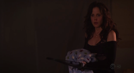 Nancy Botwin holds a crossbow, having pulled back the light blue baby blanket it was hiding under. She stands in a defunct arcade.