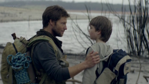 Mitchell (Jamie Bamber) reassures his son at the side of the lake on Carpathia.