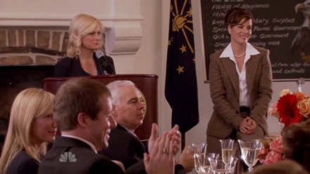 Leslie (Amy Poehler) addresses the Eagleton Public Forum while Lindsay (Parker Posey) looks on.