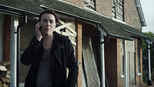 Charlie Zailers (Olivia Williams) talks on her mobile in front of a broken-down red house.