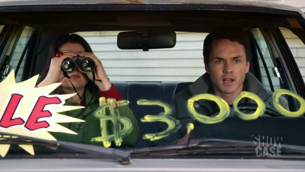 Bernie (Lauren Ash) and Terry (Paul Campbell) sit in a used car on a stakeout.