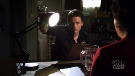 Terry (Paul Campbell) shines a lamp in Peter's (Ryan Bellevile) face during performance review.