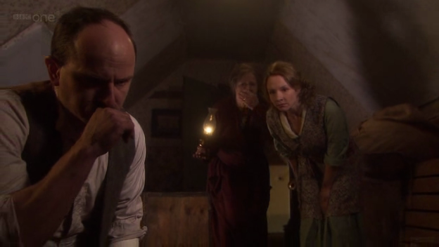 Elizabeth and Grace look on as Walter tosses objects through a hole in the wall.