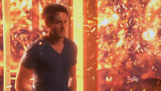 Zane (Niall Matter) stands in Cafe Diem's doorway, surrounded by an explosion.