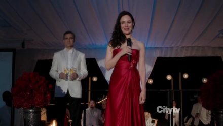 Victoria (Madeline Stowe) in a red dress, on stage.