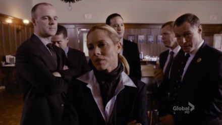 Jane Timoney (Maria Bello) surrounded by her ensemble of sexist, bullying cops.