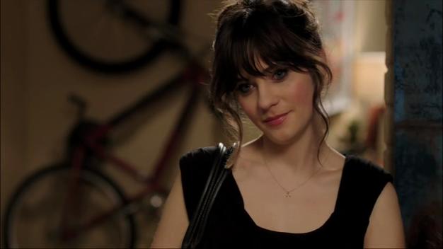 Jess (Zooey Deschanel) smiles in a black dress.